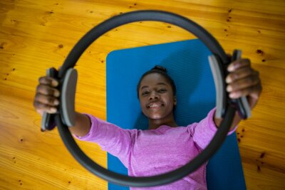 Lächelnde geeignete Frau, die mit pilates Ring auf Matte trainiert