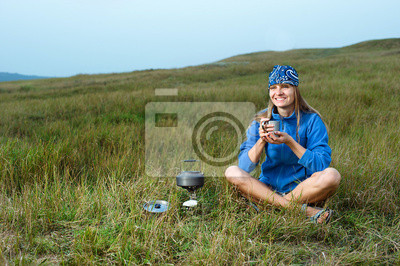 Lächelnde junge Frau Kochen auf einem Gasherd