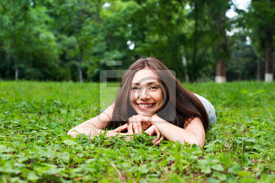 Lächelnde junge Frau liegt auf dem grünen Rasen