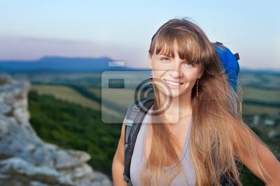 Lächelnde junge Frau mit Rucksack in den Bergen
