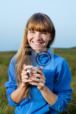 Lächelnde junge Frau mit Tasse im Freien