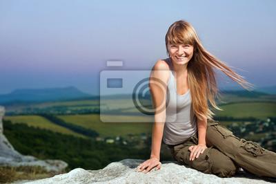 Lächelnde junge womansitting auf die des Berges