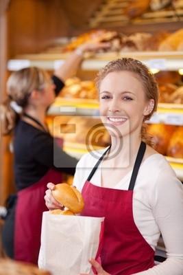 lächelnde verkäuferin packt brötchen Ein