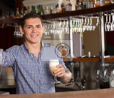 Bild Lächelnder hübscher Barmixer, der hinter dem Barzähler steht und ein Glas des geschmackvollen Cocktails hält.