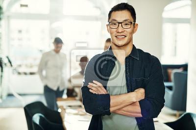 Bild Lächelnder junger asiatischer Designer mit den Kollegen, die im Hintergrund arbeiten