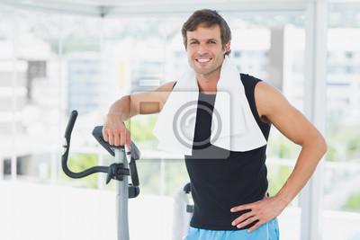 Lächelnder Mann, der an spinnender Klasse in der hellen Turnhalle steht