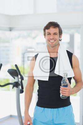 Lächelnder Mann, der Wasserflasche an spinnender Klasse in der hellen Turnhalle hält