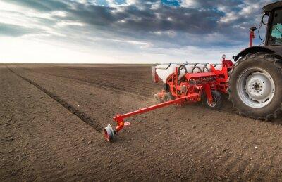 Bild Landwirt mit Traktoraussaat - Saatpflanzen auf landwirtschaftlichem Feld im Frühjahr