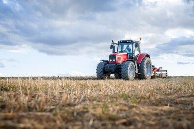 Bild Landwirtschaftliche Maschinen im Vordergrund, die Arbeit auf dem Feld durchführen.