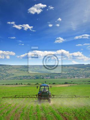 Landwirtschafttraktor Pflügen und Spritzen auf dem Feld vertikale