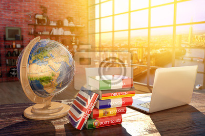 Bild Languages learning and translate, communication and travel concept, books with covers in colors of flags of Europe countries, laptop and globe on a table in a modern interior