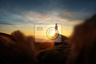 Bild Leadership And Goals. A man standning on top of a mountain watching the sun set. Conceptual photo composite.