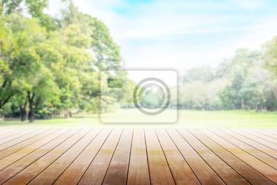Bild Leerer Holztisch mit der Partei im Gartenhintergrund verwischt.