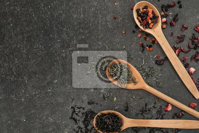 Bild Löffel mit verschiedenen Arten von trockenen Teeblättern auf grauem Hintergrund