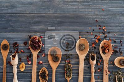Bild Löffel mit verschiedenen Arten von trockenen Teeblättern auf hölzernem Hintergrund