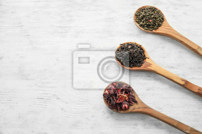 Bild Löffel mit Vielzahl von trockenen Teeblättern auf hölzernem Hintergrund