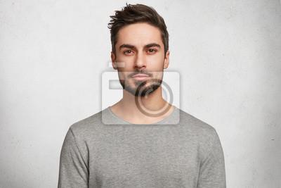 Bild Lokalisierter Schuss des jungen hübschen Mannes mit Bart, Schnurrbart und modischer Frisur, trägt zufällige graue Strickjacke, hat ernsten Ausdruck, während er auf Gesprächspartner hört, Haltungen im