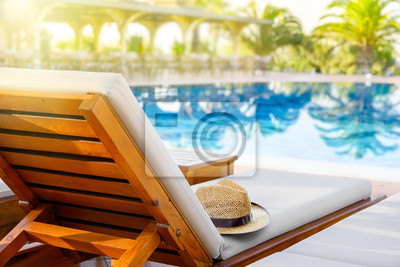 Bild Lounger with sun hat and swimming pool in luxury resort