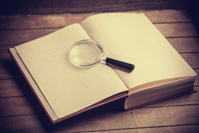 Bild Loupa und Buch auf Holztisch