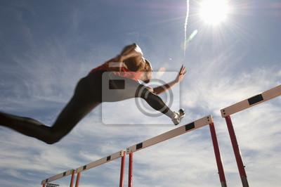 Bild Low Angle View eines männlichen Athleten springen Hürde gegen den Himmel