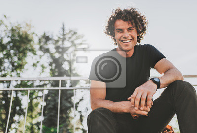 Bild Low view shot of happy stylish young man wears black t-shirt and wirstwatch on the street. Happy smiling man posing for advertisement with copy space, outdoor in the city street. People concept