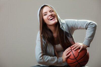 Lustige sportliche Mädchen hält Basketball Augenzwinkern