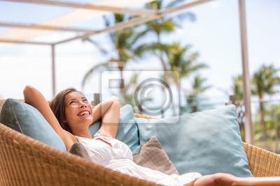 Bild Luxury hotel home living woman relax enjoying sofa furniture of outdoor patio. Beautiful young multiracial Asian girl relaxing day dreaming for rich early retirement in getaway tropical house.