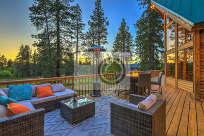 Bild Luxury summer evening mountain home eteriors with cozy porch fire table and new furniture design.