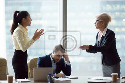 Bild Mad middle aged businesswoman have dispute with young Asian employee blaming for mistake in documents, female partners conflict arguing at business meeting, accusing in contract failure