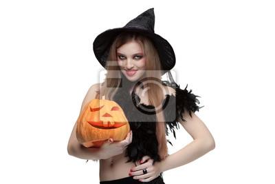 Mädchen in Hexenkostüm mit Halloween-Kürbis