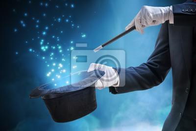Bild Magier oder Illusionist zeigt Zaubertrick. Blaues Stadiumslicht im Hintergrund.