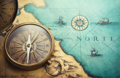 Bild Magnetic old compass on world map.Travel, geography, navigation, tourism and exploration concept background. Treasure Island on the Pirate Map.