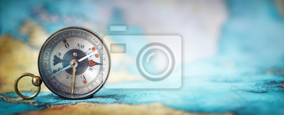 Bild Magnetic old compass on world map.Travel, geography, navigation, tourism and exploration concept wide background. Macro photo. Very shallow focus.