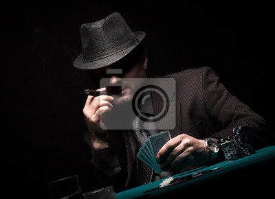 Bild Male gambler playing poker and smokes a cigar.