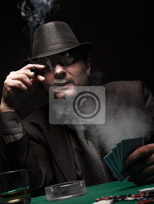 Bild Male gambler playing poker and smokes a cigar.