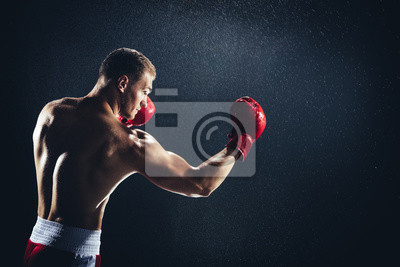 Bild Man boxing with red gloves on his hands in the rain.