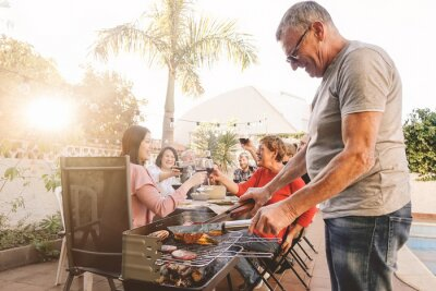 Bild Man Cooking Food On Barbecue Grill While Family Enjoying Meal In Background At Yard