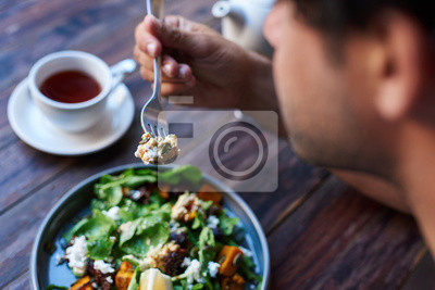 Bild Man eating delicious salad while sitting at a bistro table