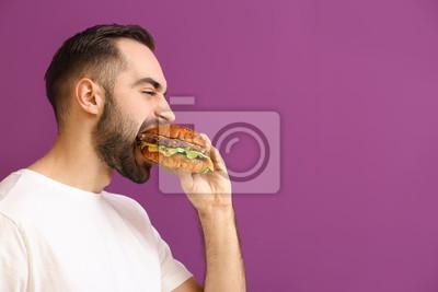 Bild Man eating tasty burger on color background