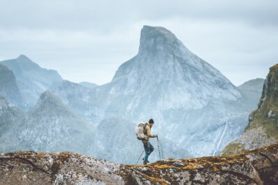 Bild Man hiking in mountains traveling solo with backpack outdoor active vacations in Norway healthy lifestyle extreme sports