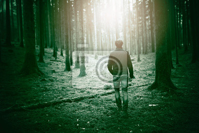 Man in dark green mossy forest landscape with mystic sunlight.