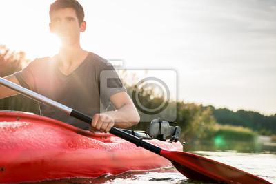 Bild Man kayaking in sunny day on lake