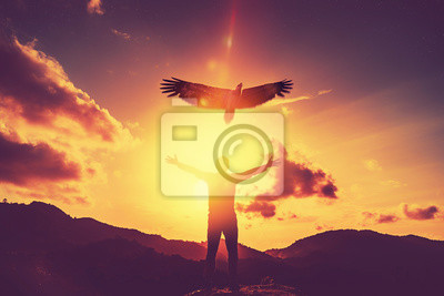Bild Man raise hand up on top of mountain and sunset sky with eagle bird fly abstract background.