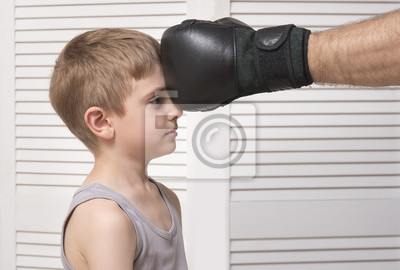 Man's hand in a boxing glove and defenseless child.