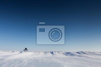 Man schiebt ein Rad auf einer schneebedeckten Oberfläche