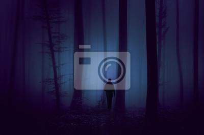 Man walks in dark violet colored foggy forest