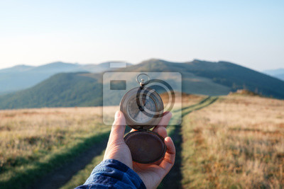 Bild Man with compass in hand on mountains road. Travel concept. Landscape photography