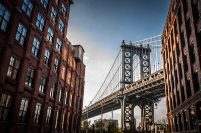 Bild Manhattan bridge seen from a narrow alley enclosed by two brick buildings on a sunny day in summer