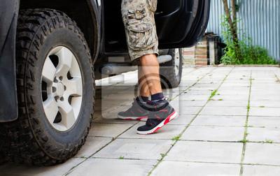 Bild Mann in den camo kurzen Hosen, die nahe bei dem LKW mit offener Tür stehen.