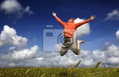 Mann springt auf einer grünen Wiese mit einem schönen bewölkten Himmel